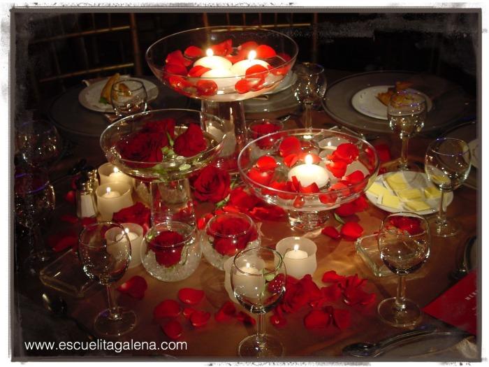 Mesa romántica con rosa, pétalos y velas.
